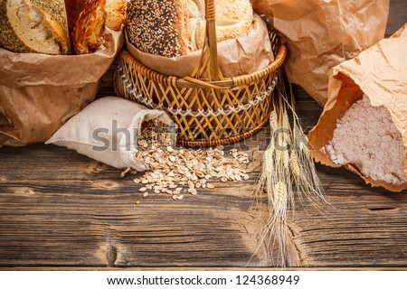 Composition with bread and rolls in wicker basket and paper bag - stock photo