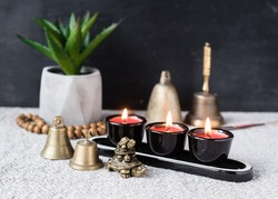 Composition with Buddhist symbols and feng shui: yin yang, turtles, aroma candles, rosaries, hand bells and plant in pot. Astrology, feng shui and zen concept