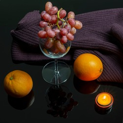 Composition with bunch of black grapes in a glass cup, oranges, a woolen scarf and a burning candle on a reflective dark shiny background