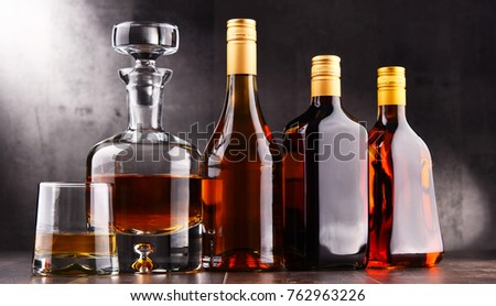 Composition with carafe and bottles of assorted alcoholic beverages. #762963226