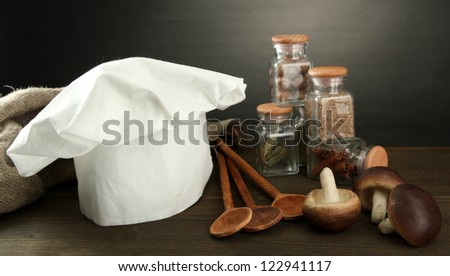 Composition with chef's hat and kitchenwear on table on grey background