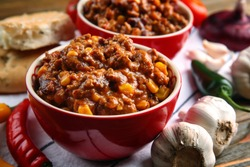 Composition with chili con carne in bowls on table