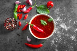 Composition with chili sauce in bowl on table