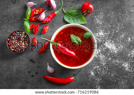 Composition with chili sauce in bowl on table #716219086