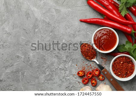 Composition with chilli pepper, powder spice, garlic and sauce on gray background Stockfoto ©