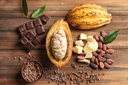 Composition with cocoa pod and products on wooden background, top view