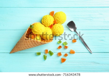 Composition with delicious ice cream in waffle cone on blue background