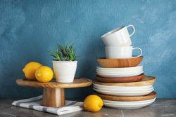 Composition with dinnerware on table against color background. Interior element
