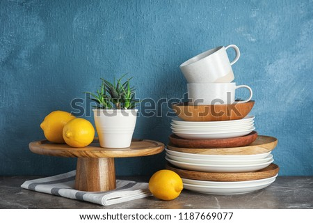 Composition with dinnerware on table against color background. Interior element stock photo