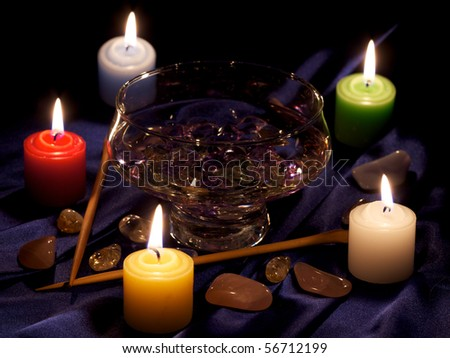 composition with five burning candles, cup with water and crystals, stones and two sticks