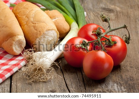 Composition with fresh bread and vegetables on old wooden table. See series