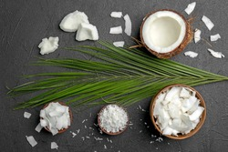 Composition with fresh coconut flakes on dark background