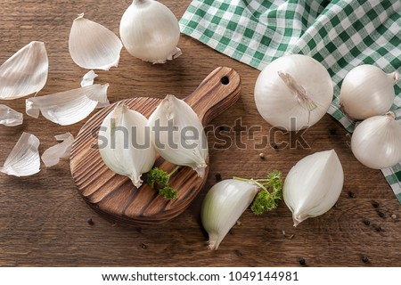 Composition with fresh cut onion and spices on wooden table