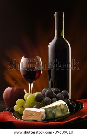 composition with glass and bottle of red wine with various types of cheese and grapes