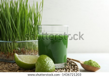 Composition with glass of wheat grass juice and lime on table against light background #1436721203