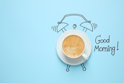 Composition with Good Morning wish and aromatic coffee on light blue background, top view. Space for text