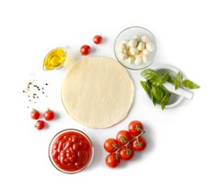 Composition with green fresh organic basil and ingredients for pizza isolated on white