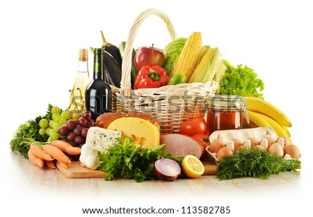 Composition with groceries in wicker basket on kitchen table