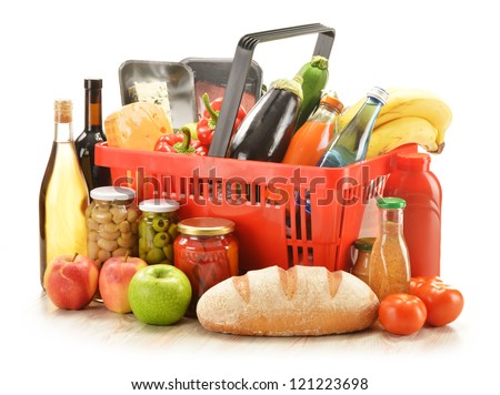 Composition with grocery products in red plastic shopping basket isolated on white background