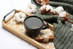 Composition with hot drink and warm plaid on white bedsheet