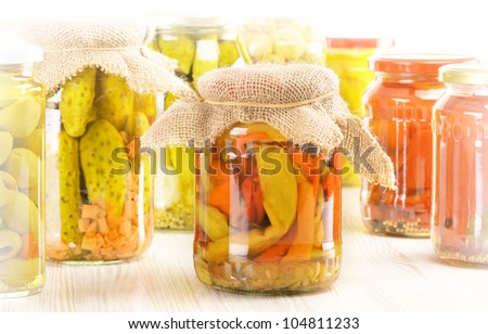 Composition with jars of pickled vegetables. Marinated food.