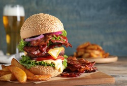 Composition with juicy bacon burger on wooden table. Space for text