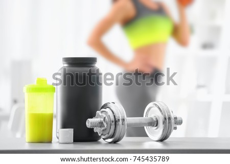 Composition with metal dumbbell, protein shake and blurred woman on background #745435789