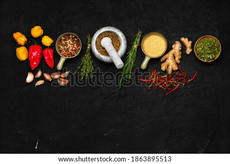 Composition with mixture of peppers, ginger, garlic, thyme, chilli and rosemary on dark background Foto stock ©