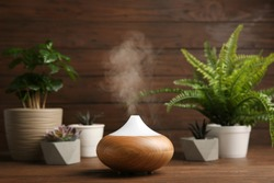 Composition with modern essential oil diffuser on wooden table against brown background, space for text