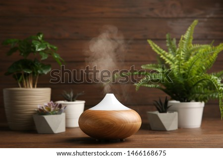 Photo of  Composition with modern essential oil diffuser on wooden table against brown background, space for text
