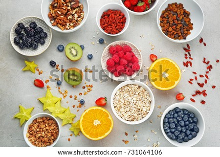 Composition with nutritious oatmeal and different ingredients for breakfast on light background #731064106
