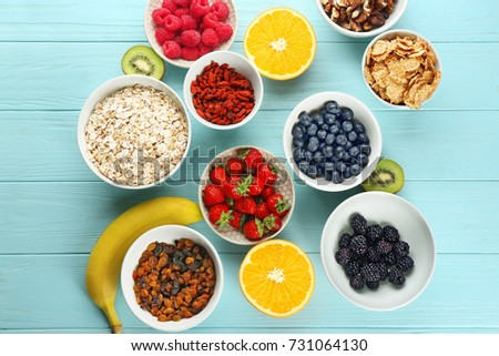 Composition with nutritious oatmeal and different ingredients for breakfast on wooden background #731064130