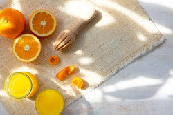 composition with oranges next to juicer and orange juice with rays and sun shadows