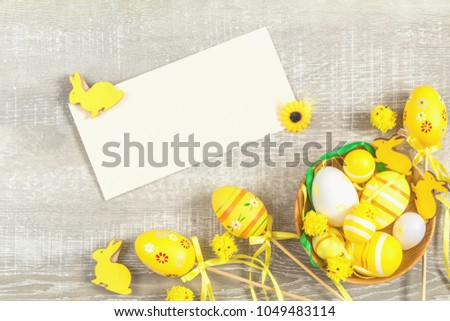Composition with painted eggs and other easter attributes and accessories in yellow tones on a light wooden surface. Top view, postcard for writing, copy space