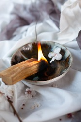 Composition with peruvian palo santo holy wood on handmade ceramic plate, white candle and bottle with banch of blooming almand tree. Esoteric objects for meditation. Antistress and relaxation.