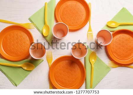 Composition with plastic dishware on wooden background, flat lay. Picnic table setting #1277707753