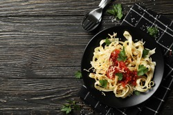 Composition with plate of tasty pasta on wooden background