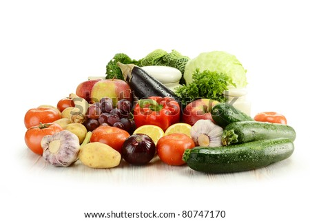 Composition with raw vegetables and kitchen dishes isolated on white