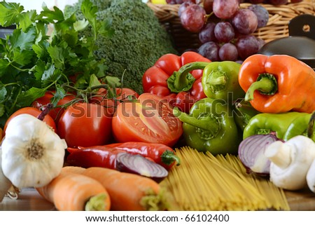 Composition with raw vegetables and spaghetti on kitchen table