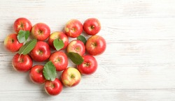 Composition with red apples on white wooden background, space for text
