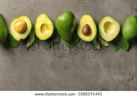 Composition with ripe avocados on dark grey background