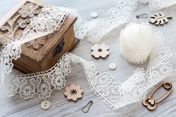 Composition with sewing tools: ivory thin lace, small light buttons, wooden flat flowers and safety pin as decor, wooden carved box and light candle wrapped in lace on the rustic surface. Flat lay