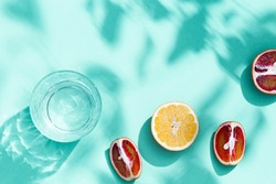 Composition with slices grapefruit, red orange, lemon and drink glass on turquoise colored background. Summer time flat lay with daylight.
