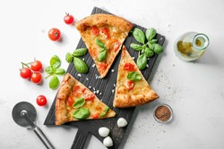 Composition with slices of delicious pizza Margherita on light background