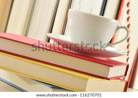 Composition with stack of books and cup of coffee