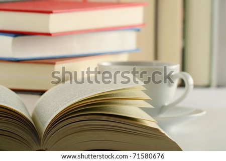 Composition with stack of books and cup of coffee on table