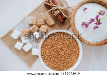 Composition with sugar, different types of sugar, cane and white, lump and sugar sand. Top view, rustic