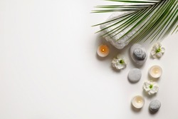 Composition with symbolic objects for spa salon. Stone therapy attributes for cosmetic procedures. Conceptual image, rocks and flowers representing balance. Close up, copy space, top view, background.