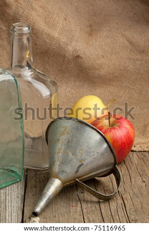 Composition with tow vintage bottles, fresh apples and old metal funnel on old wooden table with sacking as background