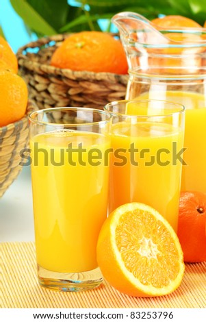 Composition with two glasses of orange juice, fruits and pitcher